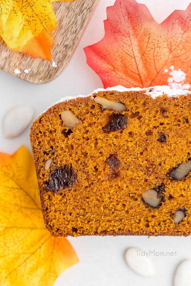 slice of pumpkin bread on a counter with fall leaves