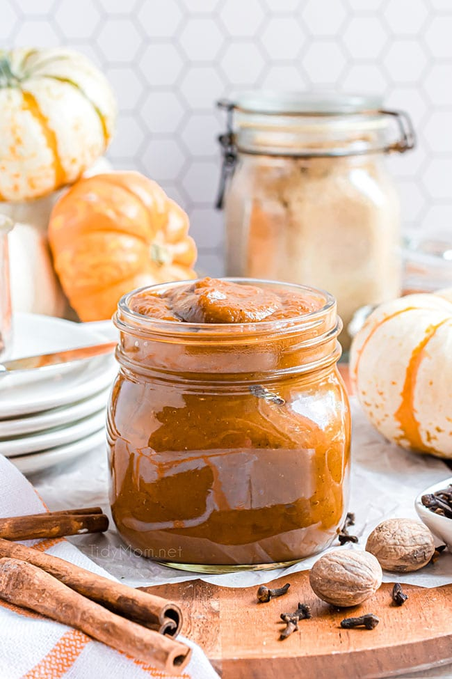 pumpkin butter in a jar with pumpkins on the counter