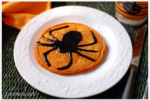 Pumpkin Pancake decorated with black cinnamon syrup spider.